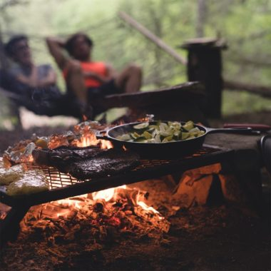 A skillet full of food sitting over fire
